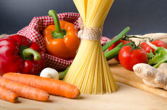 Composition of uncooked spaghetti and different types of vegetab Stock Photos