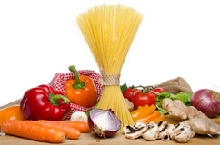 Composition of uncooked spaghetti and different types of vegetab Stock Image