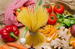 Composition of uncooked spaghetti and different types of vegetab Stock Images