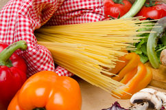 Composition of uncooked spaghetti surrounded by vegetables Stock Image
