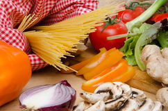 Composition of uncooked spaghetti surrounded by vegetables Royalty Free Stock Photo