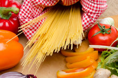Composition of uncooked spaghetti surrounded by vegetables Royalty Free Stock Photography