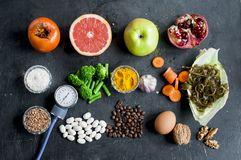 Composition of useful food for the vascular system in the body. With a blood pressure tonometer, flat lay on dark background Royalty Free Stock Photo