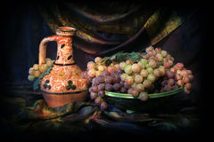 Composition of Uzbek traditional ceramic water vesel, ceramic dish and grapes Royalty Free Stock Photo