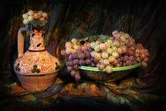 Composition of Uzbek traditional ceramic water vesel, ceramic dish and grapes Royalty Free Stock Image