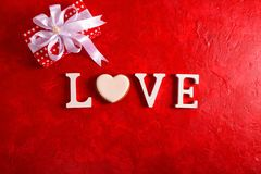 Composition for Valentine`s Day on a red background with white letters and a heart. Top view. stock image