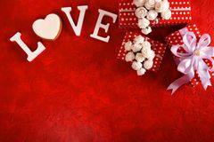 Composition for Valentine`s Day on a red background with white letters and a heart. Top view. stock photos
