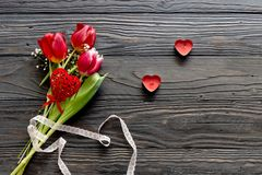 Romantic bouquet of tulips and red candles. Composition for Valentine`s Day. Romantic bouquet of tulips and red candles on a wooden table close-up Stock Image