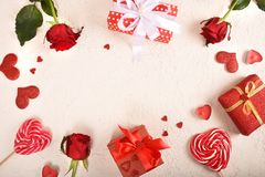 Composition for Valentine`s Day. Roses, gift, glasses and wine, red hearts. Top view. stock image