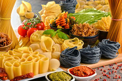 Composition with variety of pasta on kitchen table Stock Image