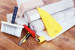 Composition with various tools for home repair and rolls of wallpaper Royalty Free Stock Photo