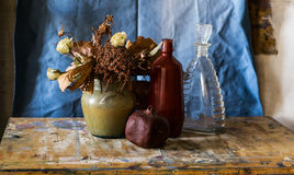 Composition of vase, bottles, pomegranate and withered flowers Royalty Free Stock Photo