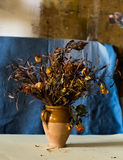 Composition of a vase filled with withered flowers Royalty Free Stock Images