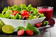 Composition with vegetable salad bowl and glass of juice Royalty Free Stock Photography