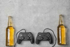 Composition with video game controllers and beer. On grey background Royalty Free Stock Photography