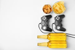 Composition with video game controllers, beer. And snack on light background Royalty Free Stock Image