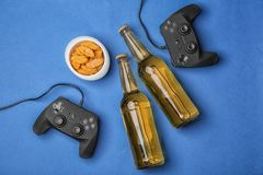 Composition with video game controllers,. Beer and snack on color background Stock Photography