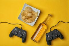Composition with video game controllers. Beer and snack on color background Royalty Free Stock Images