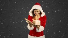Composition visuelle avec la neige en baisse au-dessus de la fille en cadeau de participation de costume de Santa banque de vidéos
