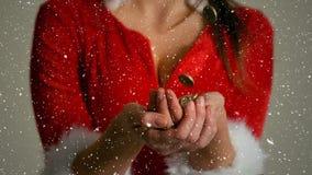 Composition visuelle avec la neige en baisse au-dessus de la fille dans le costume de Santa tenant des mains ensemble banque de vidéos