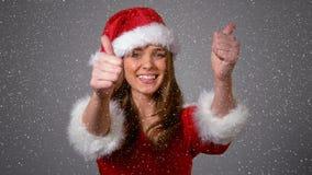 Composition visuelle avec la neige en baisse au-dessus de la fille heureuse dans le costume de Santa montrant des pouces  banque de vidéos