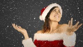 Composition visuelle avec la neige en baisse au-dessus de la fille heureuse dans le costume de Santa montrant les paumes ouvertes banque de vidéos