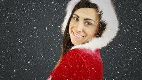 Composition visuelle avec la neige en baisse au-dessus de la fille de sourire dans le costume de Santa tout en tournant banque de vidéos
