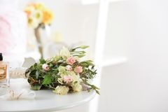 Composition with wedding rings and bouquet of flowers. On table Stock Image