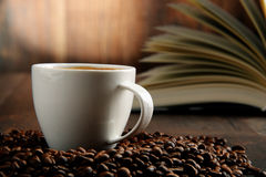 Composition with white cup of coffee and open book Stock Photos