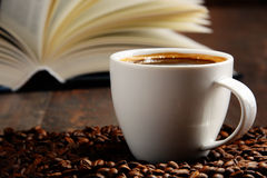 Composition with white cup of coffee and open book Royalty Free Stock Image