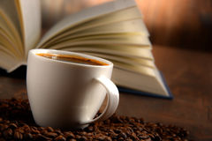 Composition with white cup of coffee and open book Stock Photography