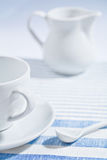 Composition of white cup and spoon and jug Royalty Free Stock Photos