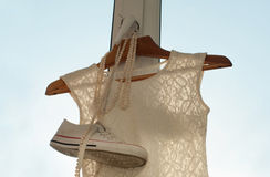 A composition with a white lace dress, a pair of sneakers  and a pearl necklace hanging on a wooden clothes hanger on a window gri Stock Image