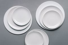 Composition of white plates. On grey background stock photos