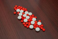 Composition of tablets. Composition of white and red tablets lying on the table Stock Photo