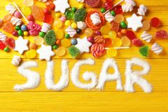 Composition with white sugar and variety of candies. On yellow wooden background stock image