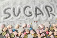 Composition with white sugar and variety of candies. On grey background royalty free stock image