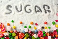 Composition with white sugar and variety of candies. On grey background stock photography