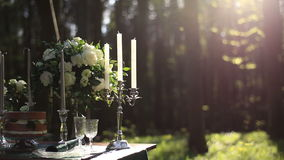 Composition of white vintage candelabrum and white roses bouquet on the wedding decorated table in the forest. Romantic. Dinner in the woods stock video footage