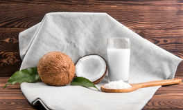 A composition of whole and cut tasty coconuts and a glass full of milk and spoon with coconut chips on a fabric on a wooden table. Royalty Free Stock Photography