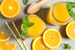 Free Composition With Orange Pieces, Mint, Tubules, Wooden Juicer And Glass Jars With Fresh Orange Juice On Grey Background Royalty Free Stock Image - 147134266