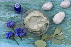 Essential oil with cosmetic clay and flower and branch of eucalyptus, stones, for spa treatments, in glass bowl on old Royalty Free Stock Image