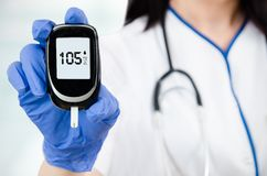 Composition of woman doctor holding glucometer. Royalty Free Stock Photo
