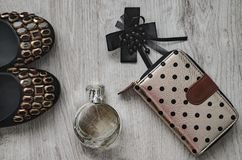 Shoes, perfume, bow, purse. Composition, women`s shoes with colorful large rhinestones, a black bow, perfume in a glass bottle and a purse on a wooden Stock Photo