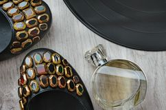 Women`s shoes, a bottle of perfume and a fragment of a large vinyl plate. Composition, women`s shoes with colorful rhinestones, a bottle of perfume and a Royalty Free Stock Photography