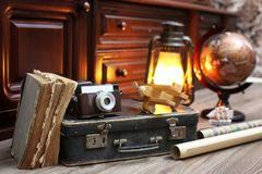 Composition on a wooden floor vintage globe with old leather sui. Tcase with objects for travel Royalty Free Stock Image