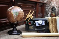 Composition on a wooden floor vintage globe with old leather sui. Tcase with objects for travel Royalty Free Stock Photography