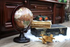 Composition on a wooden floor vintage globe with old leather sui. Tcase with objects for travel Stock Photos
