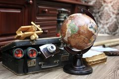 Composition on a wooden floor vintage globe with old leather sui. Tcase with objects for travel Royalty Free Stock Images