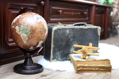 Composition on a wooden floor vintage globe with old leather sui. Tcase with objects for travel Royalty Free Stock Photo